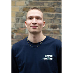 Man smiling wearing navy blue organic cotton long sleeve t-shirt with white Goose Studios text logo on left chest