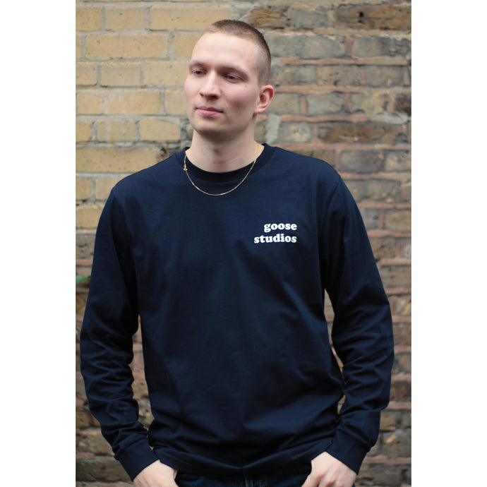 Man wearing navy blue organic cotton long sleeve t-shirt with white Goose Studios text logo on left chest