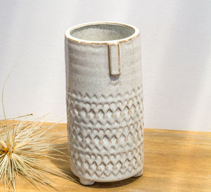 Tall white ceramic vase with face imprint