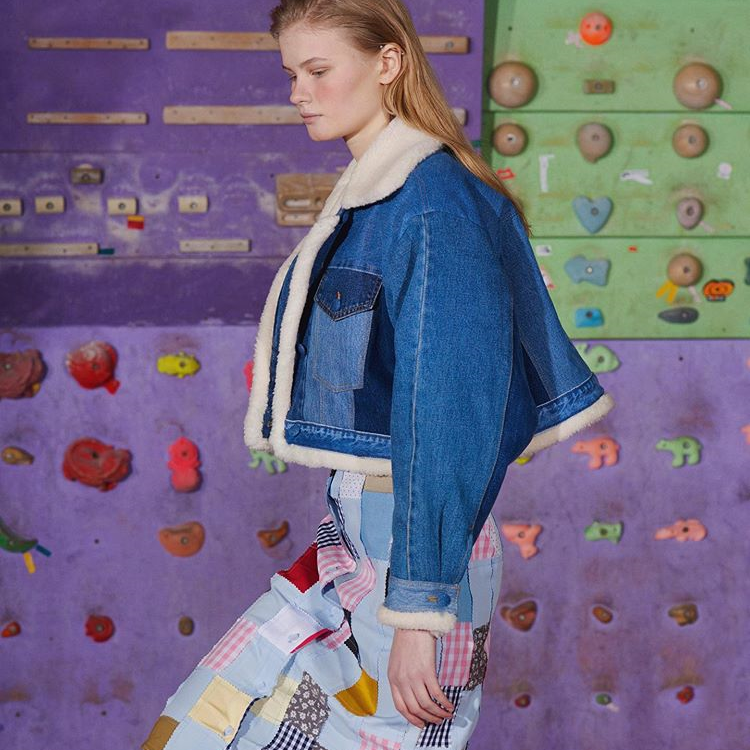 girl in crazy skirt and denim jacket, with climbing wall behind, nobelz style market second hand