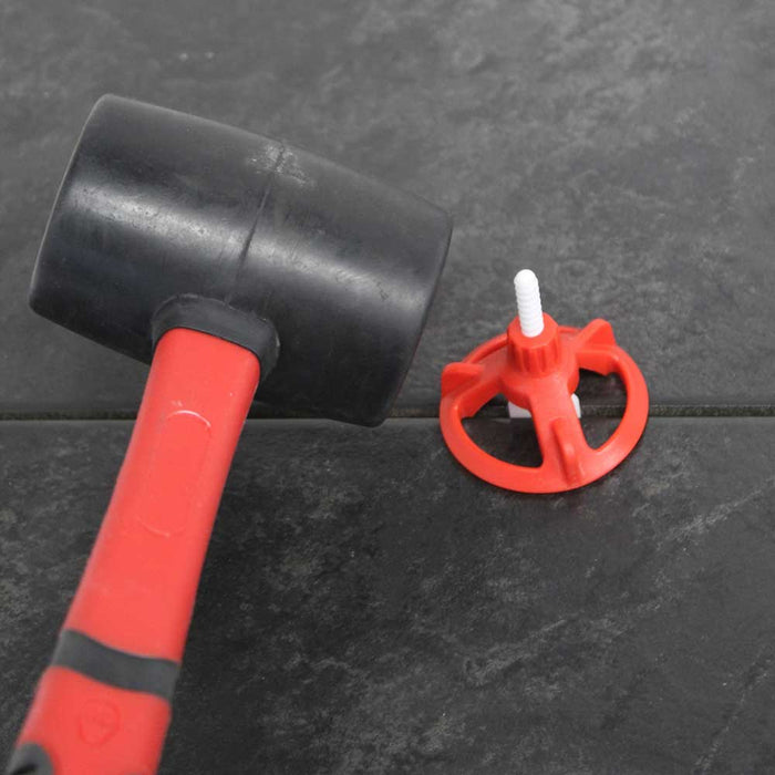 Use RTC mallet to knockout tile leveling system clip assembly after tile is set