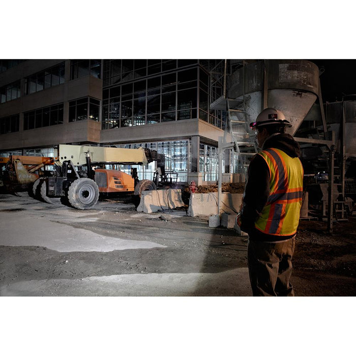 Construction worker lighting up jobsite with Milwaukee USB Hard Hat Headlamp