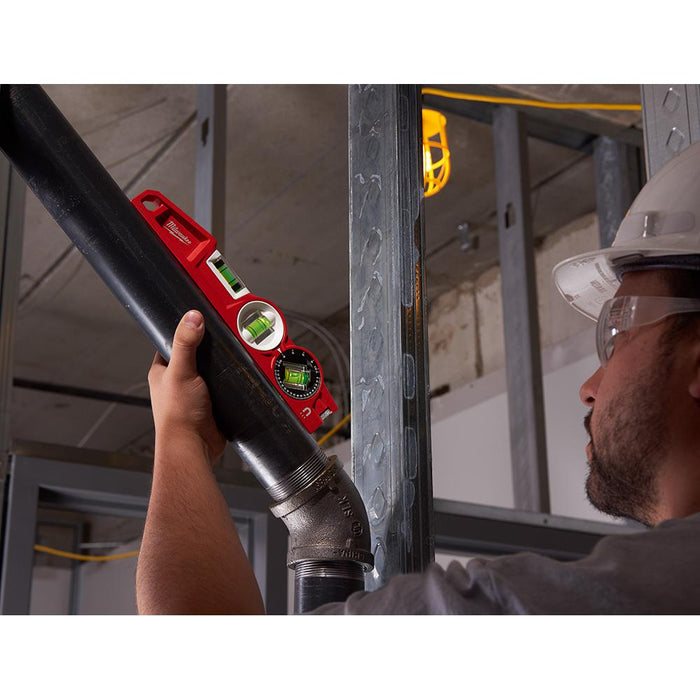 Professional measuring the angle of a pipe installation with Milwaukee torpedo level