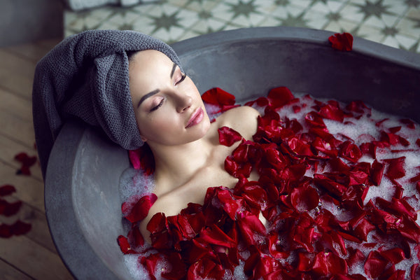 relaxing in a bath with rose petals