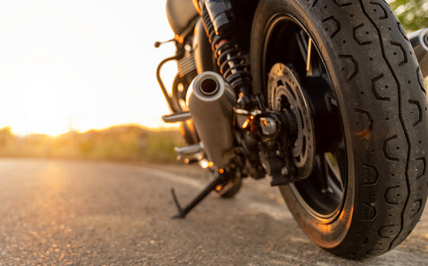 View of the back wheel and exhaust of a motorcycle and ground with the sunset peaking out from the horizon