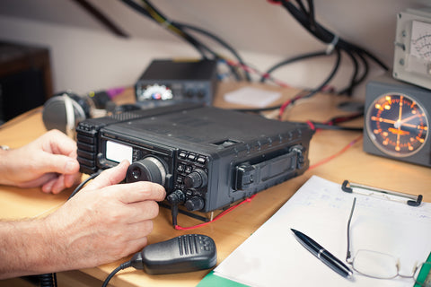 View of hands adjusting ham radio equipment