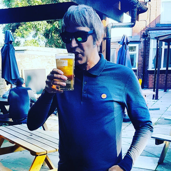 Man drinking a pint of lager in a beer garden wearing a From The Terraces Long sleeve polo