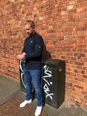 Man standing in front of wall wearing a From The Terraces white navy long sleeve polo shirt