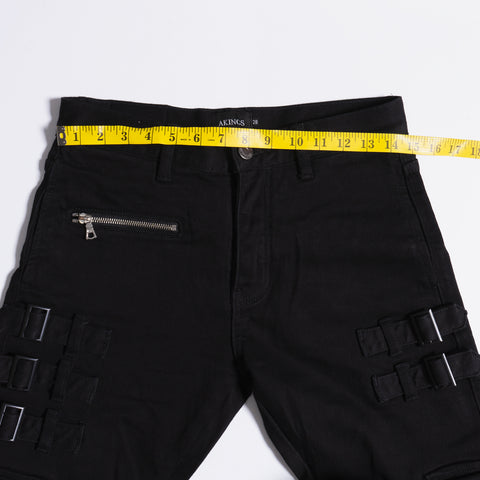 Measuring waistband of black jeans