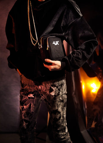 Crossbody shoulder bag styled with pants chains and velour hoodie