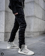 Waist down photo with blacked stacked pants and sneakers