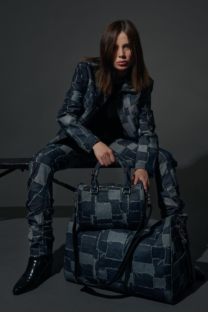 female model sitting on bench with the patchwork 45 duffle bag and the patchwork nano bag on the floor in front of her