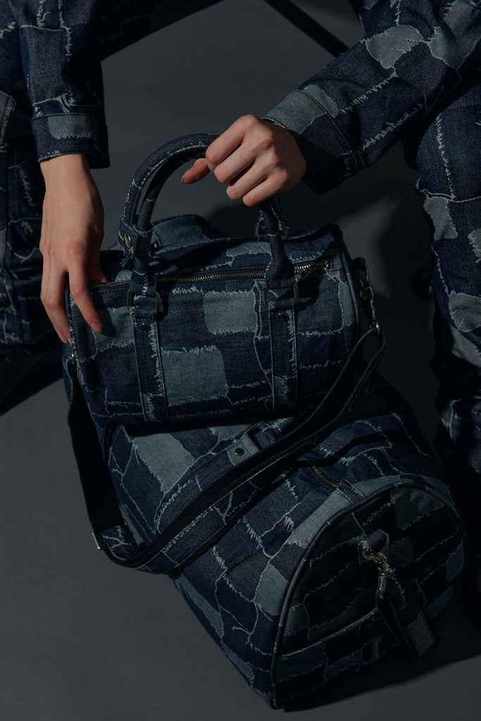 model's hand holding the patchwork nano bag on top of the patchwork 45 duffle bag
