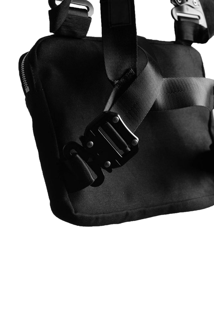 close up angled view of the back of the ak01 chest bag. shows the buckle detail on the straps.