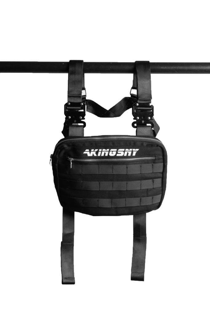 front of the ak01 chest bag hanging from a black pole. shows akingsny logo on bag and horizonal zipper under the logo