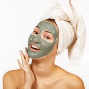 Smiling woman having a spa day with the detoxifying green clay face mask on her face. Hello Wellness Naturals
