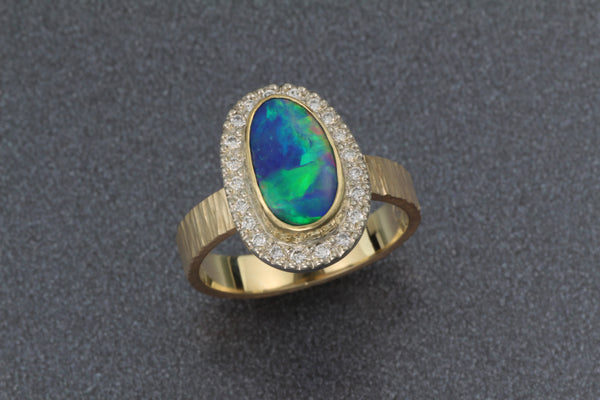 Stunning gold ring set with an opal doublet with a diamond halo