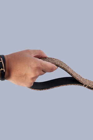 hand holding natural rubber dog lead by the handle