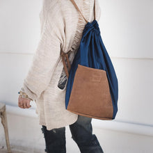 Load image into Gallery viewer, Close up photo of a female's back, cropped from shoulders to knees. Dressed casually, on her back she is wearing a handmade, Meridian bag