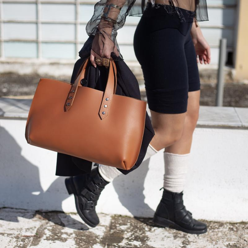 Photo of female, cropped from waist to floor.  She is holding a handmade, brown, leather Jet Set Mini bag