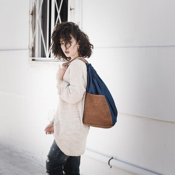 Open shot photo, of a brunette female, dressed casually. Over her shoulder, and onto her back, she is holding a handmade, Meridian, bag, by 3rd Floor