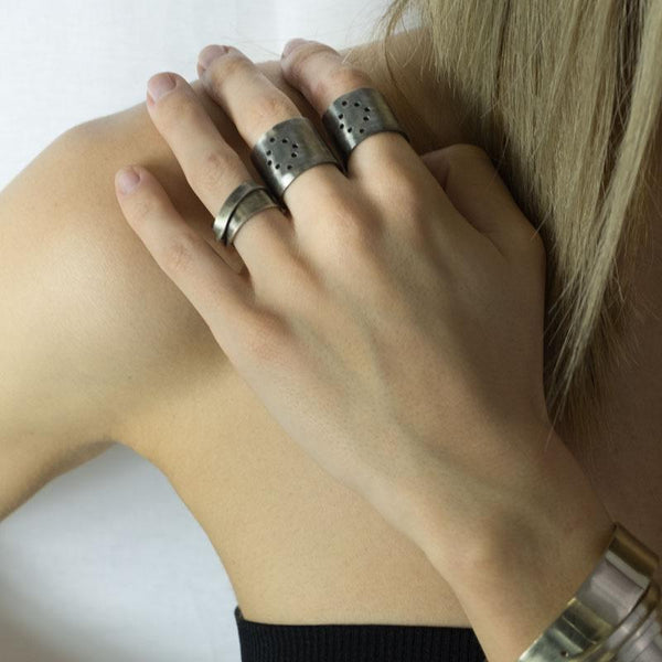 Girls hand. She is wearing 3rd Floor Handmade rings on her index, middle and wedding ring fingers