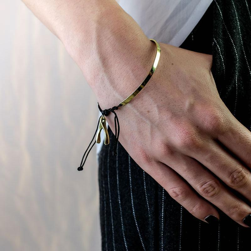 Cropped photo of female's hand, from forearm to fingers. Thumb is in a pocket. On her wrist a gold, black cord and wishbone charm, bracelet