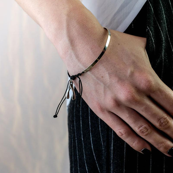 Cropped photo of female's hand, from forearm to fingers. Thumb is in a pocket. On her wrist a silver, black cord and wishbone charm, bracelet