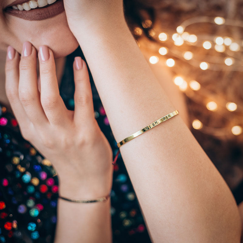 Close up photo of female, with her hands touching her chin, and mouth. She is smiling. On either wrist she is wearing gold bracelets