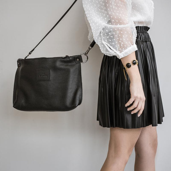 woman wearing, city clutch leather bag,by 3rd-floor, workshop