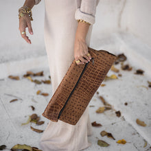 Load image into Gallery viewer, Female in long, beige dress, holding a caramel colored, Croco bag, in her left hand