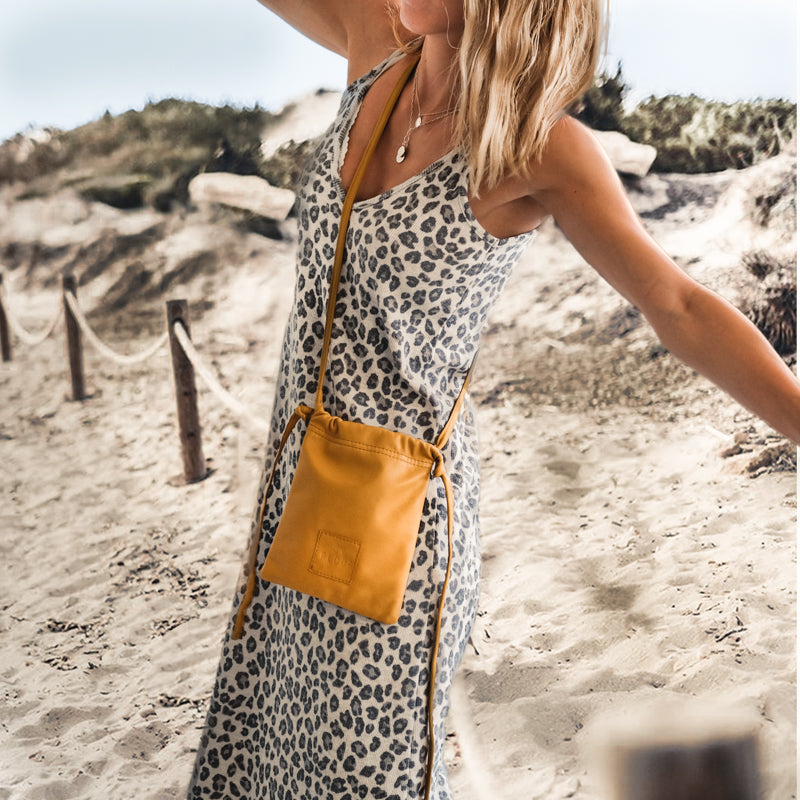 Blond girl on the beach, wearing a printed dress. She is wearing a yellow, post cross, Gogo bag by 3rd Floor