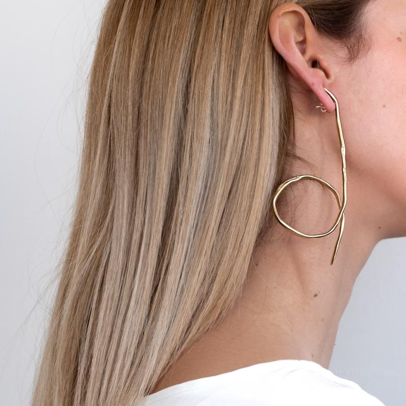 Blond girl, wearing long, gold, earrings with a loop like finish on the bottom