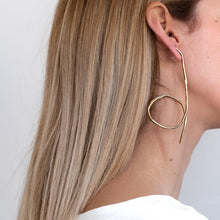 Load image into Gallery viewer, Blond girl, wearing long, gold, earrings with a loop like finish on the bottom