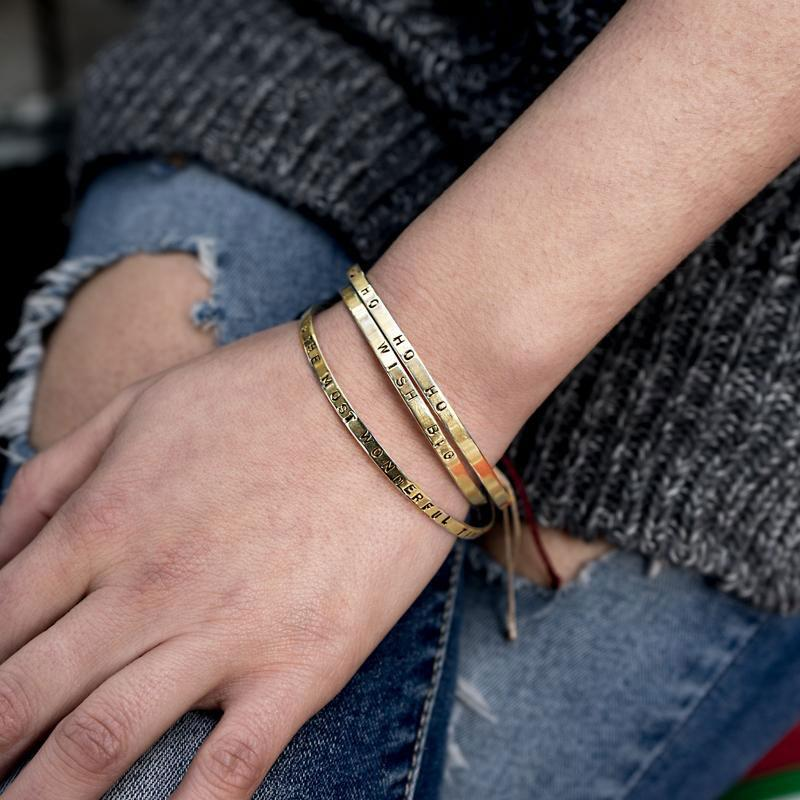 Close up of left hand, rested on a right thigh. Underneath the hand, a torn jean can be seen. On her wrist, three gold bracelets are worn