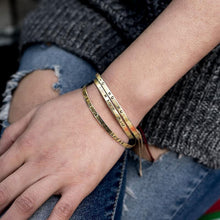 Load image into Gallery viewer, Close up of left hand, rested on a right thigh. Underneath the hand, a torn jean can be seen. On her wrist, three gold bracelets are worn