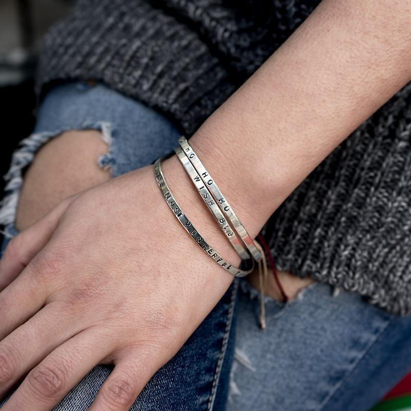 Close up of left hand, rested on a right thigh. Underneath the hand, a torn jean can be seen. On her wrist, three silver bracelets are worn