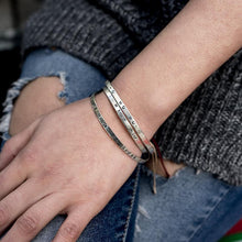 Load image into Gallery viewer, Close up of left hand, rested on a right thigh. Underneath the hand, a torn jean can be seen. On her wrist, three silver bracelets are worn