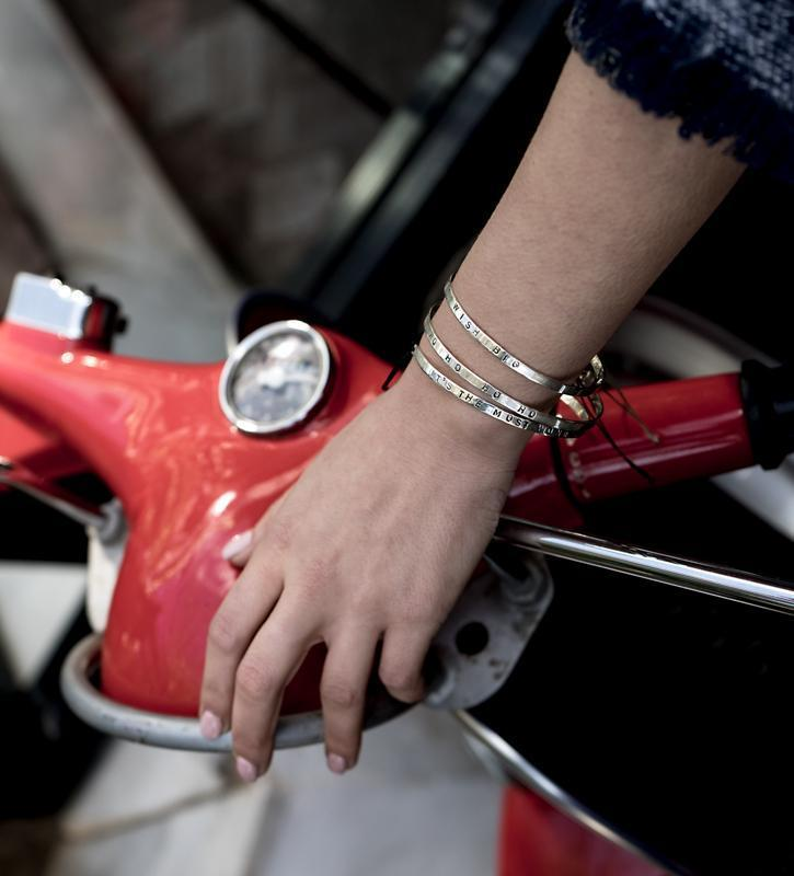Photo of left hand, rested on the front and top side, of a red motor bike. On the wrist, three silver bracelets are worn