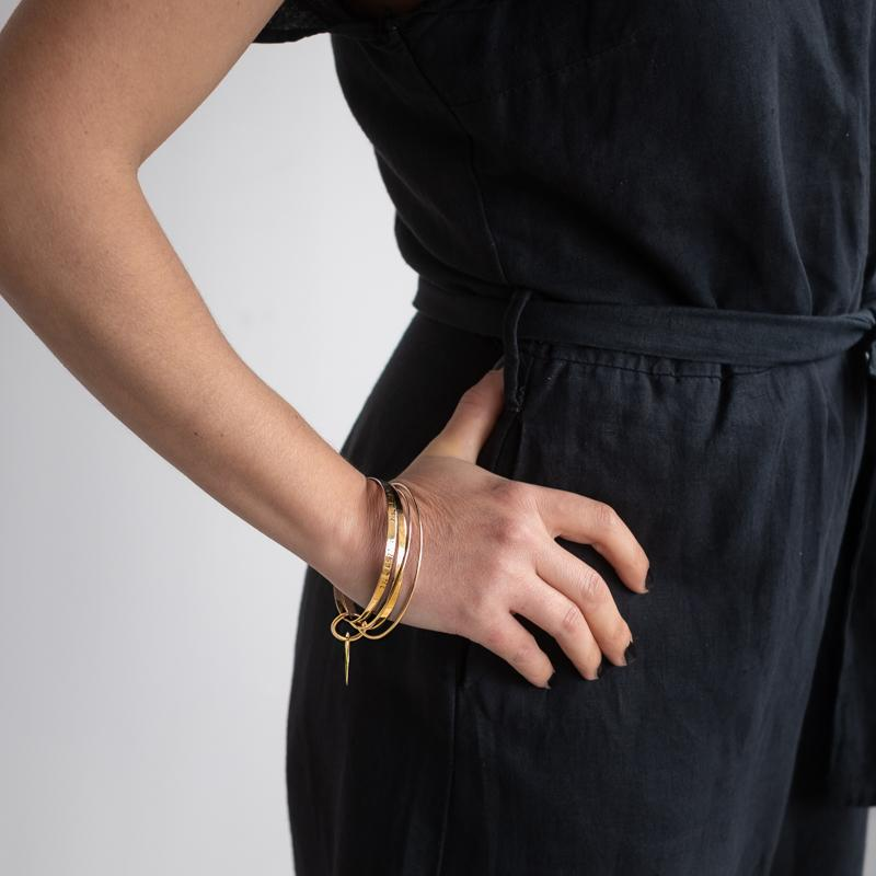 woman in black right hand on hip wearing a gold multi bangle bracelet by 3rd Floor Coordinates Line