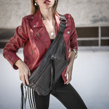 Load image into Gallery viewer, Girl in black trouser,and a red jacket. She is wearing a Bravado, black leather, fanny pack, crossed over her chest