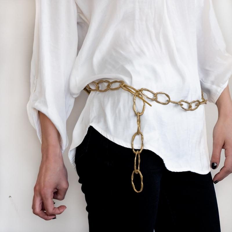 Girl in black pants and white shirt, wearing a gold plated, handmade, loop belt
