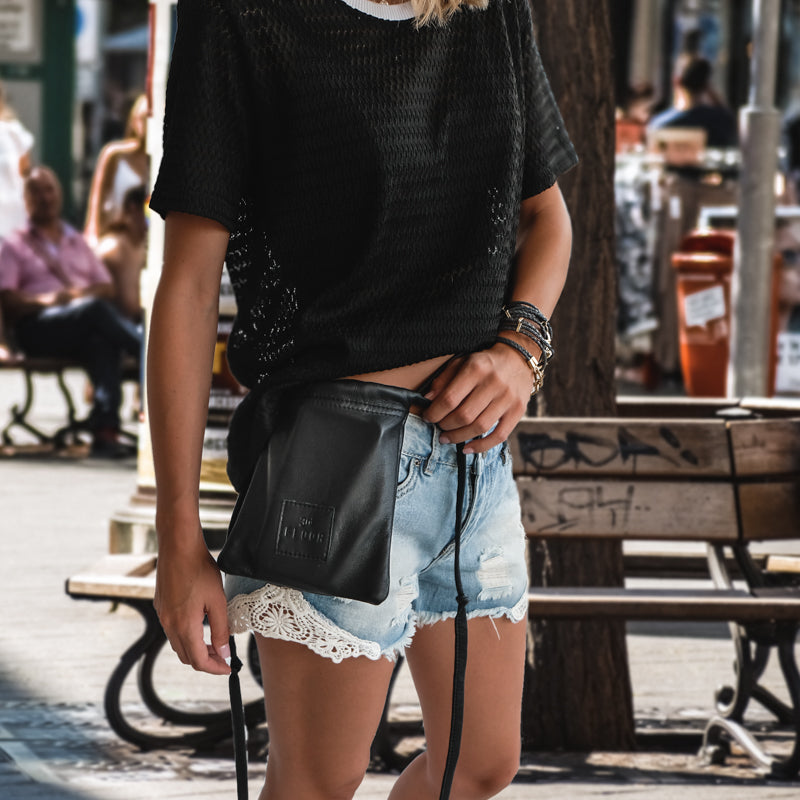 Girl wearing a black tshirt, and blue jean shorts. She is wearing a black, leather, handmade Gogo bag by 3rd Floor