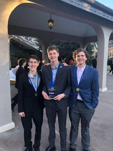 Carter Galyardt, Rowan Steger, and Colin Patterson holding their DECA State second place award in front of The Broadmoor Hotel in Colorado Springs, Colorado