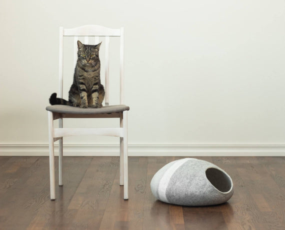 FURST - Adorable cat on a chair next to its felt Mineral cocoon den in silver shades with a white ring