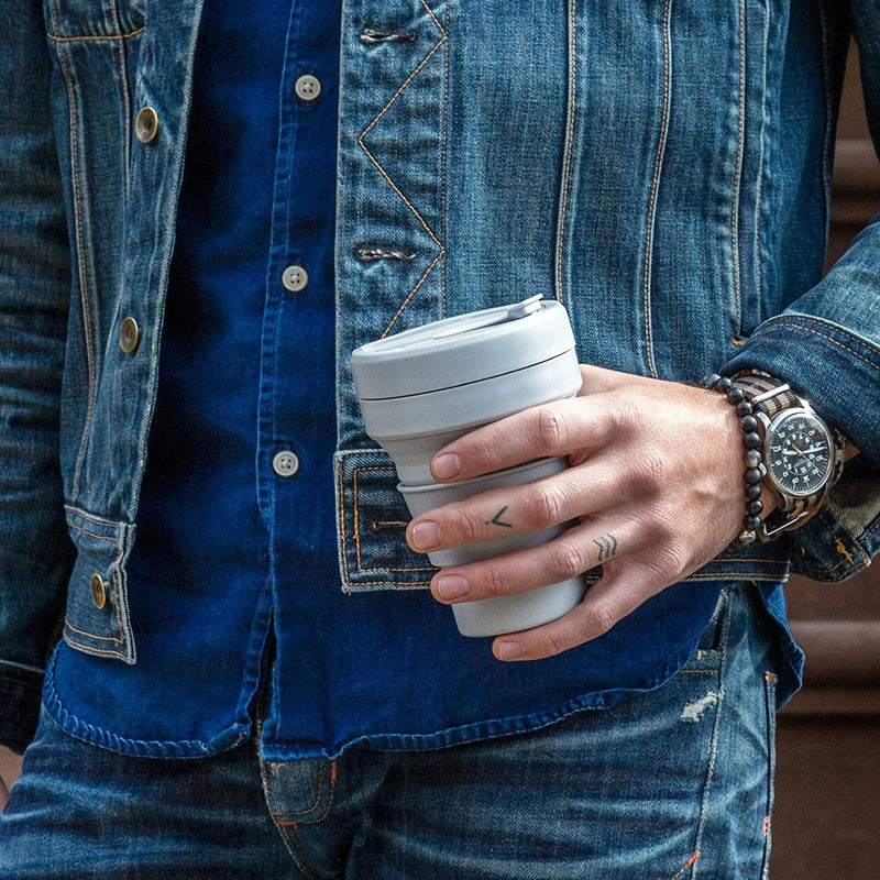 a guy holding a reusable and collapsible coffee cup by stojo in cashmere colour