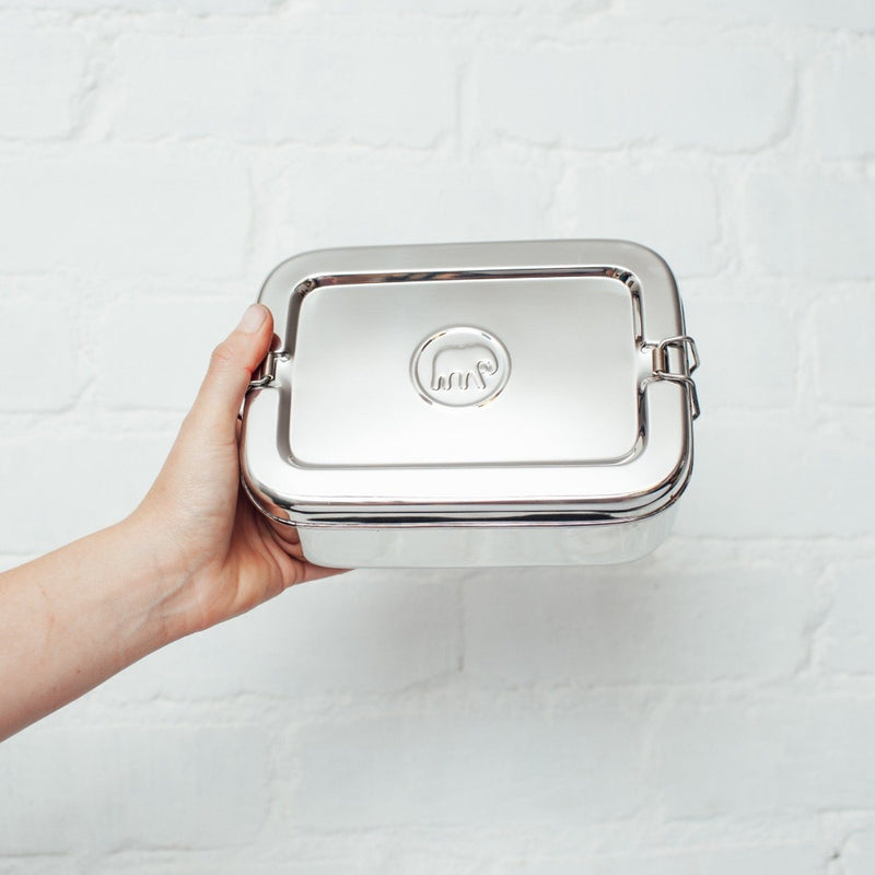 A hand holding a sustainable stainless steel lunchbox by The Elephant Box