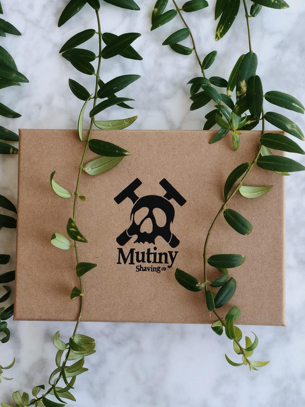 Plastic free and vegan shaving kit containing a double edge safety razor, wooden shaving brush, a natural shaving soap and replacement blades in a recyclable box by Mutiny Shaving