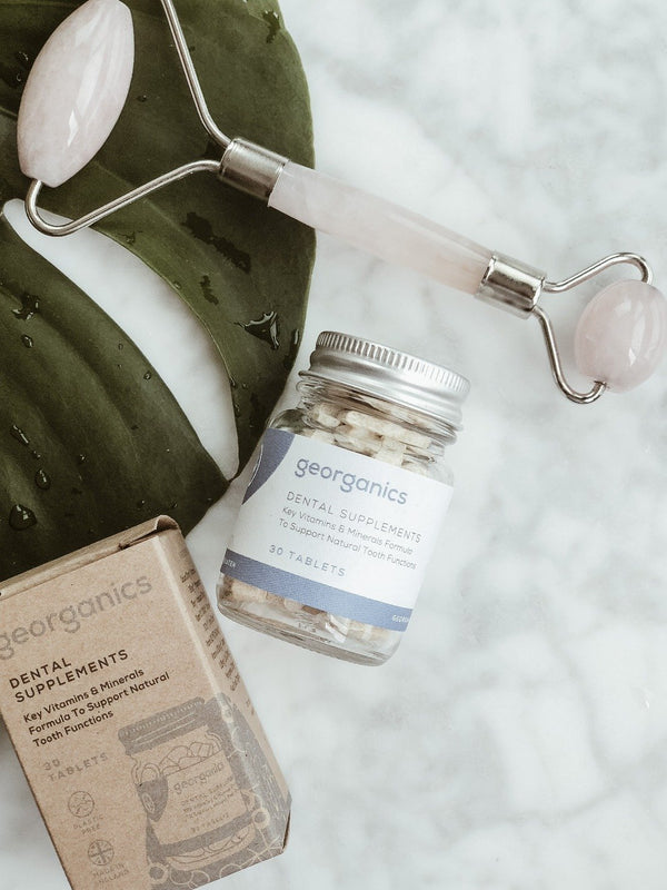 Recyclable jar of natural and organic dental supplements with its plastic-free packaging on white marble