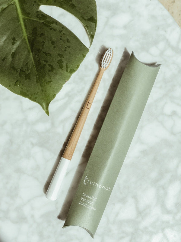 A sustainable white bamboo toothbrush along with its plastic free packaging on white marble